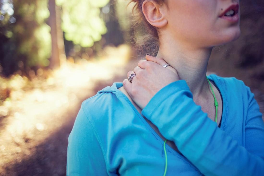 Woman with injury to collarbone joint holding neck and shoulder while outside running.