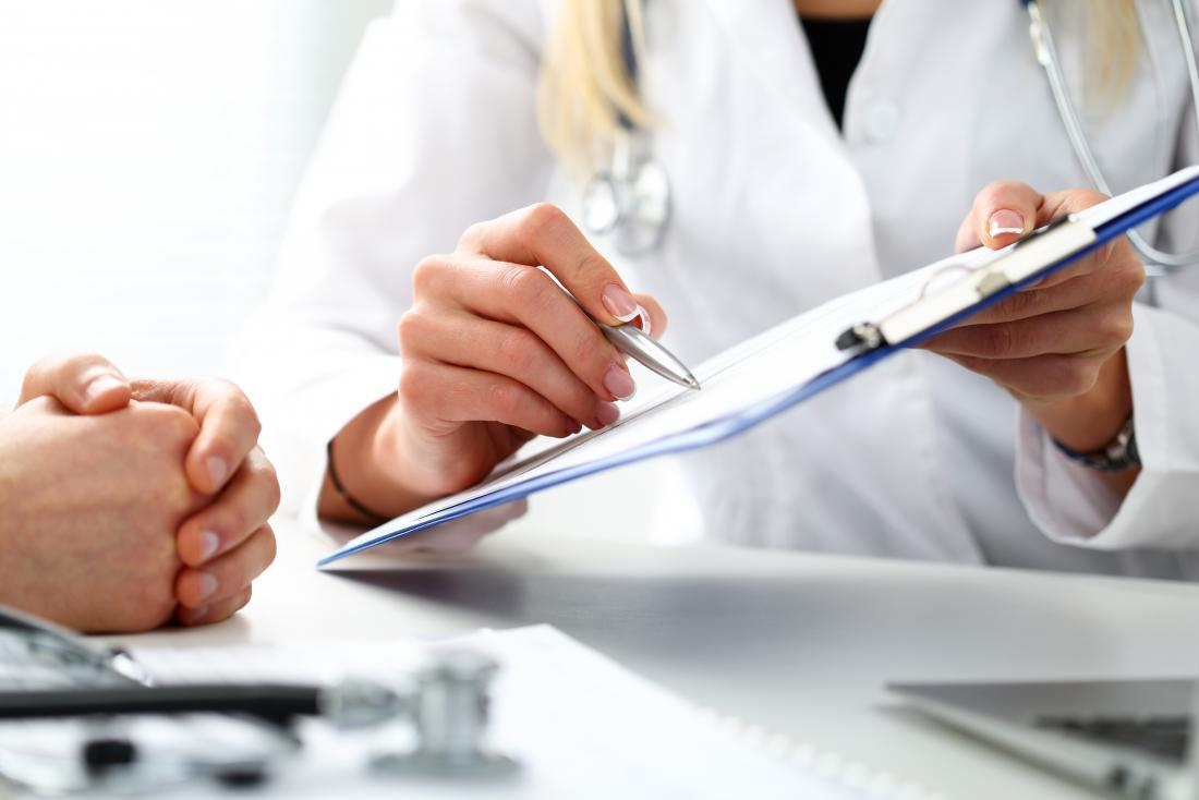 Doctor with a clipboard showing it to patient to discuss results.