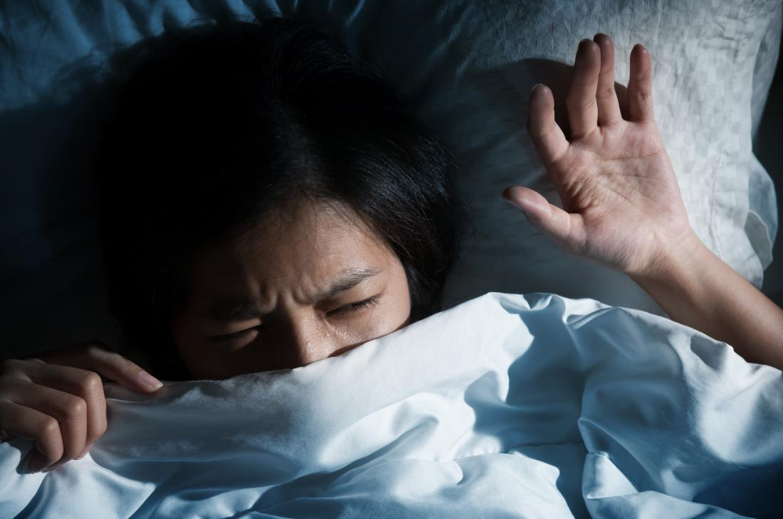 terrified woman in bed