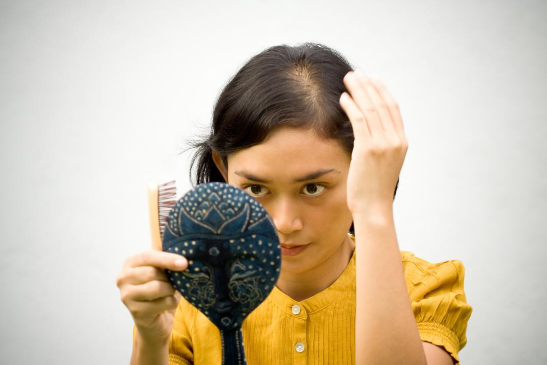 Woman looking into the mirror with iron deficiency hair loss
