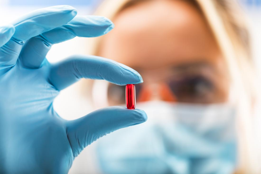 scientists holding red pill