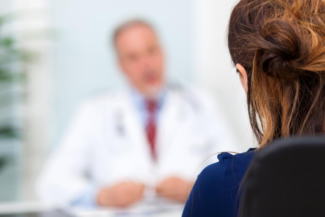 a doctor in the background speaking to a patient in the foreground about an Adderall crash