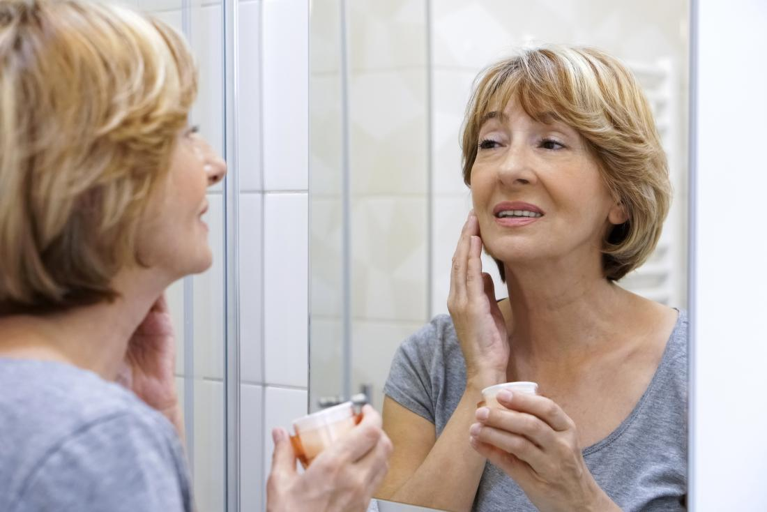 woman using moisturizer on her face to help with menopause rash