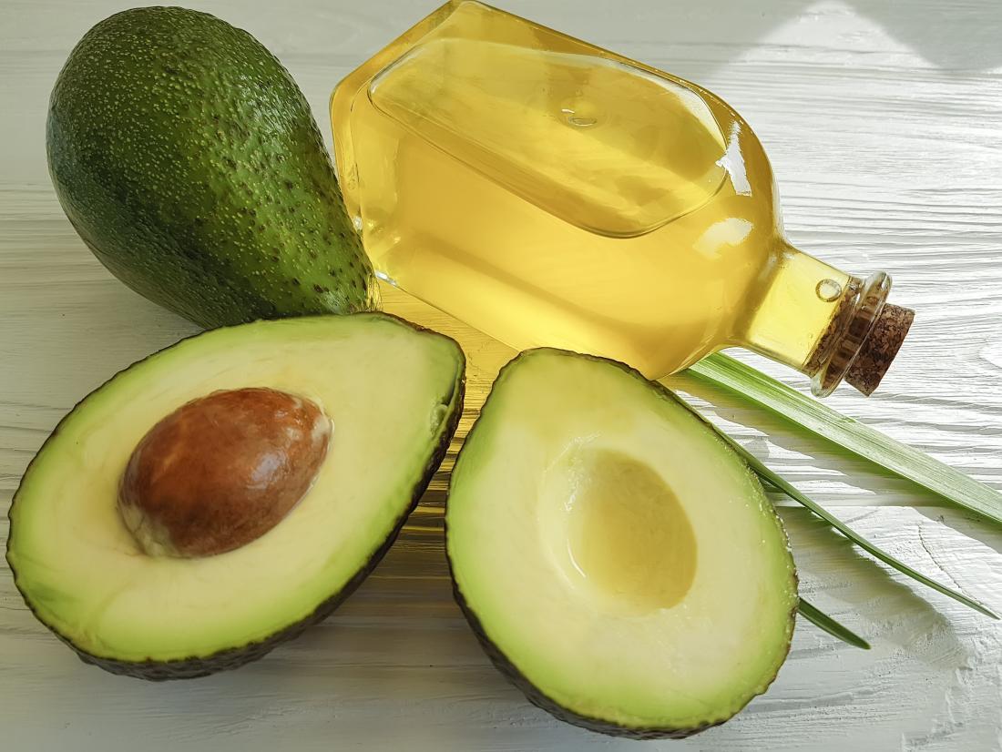 Avocado oil in jar next to halved avocado.