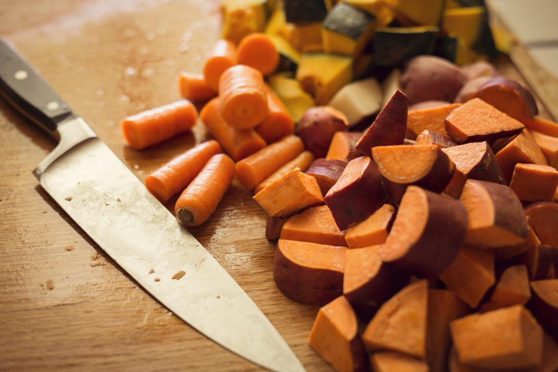 carrots and sweet potato with knife