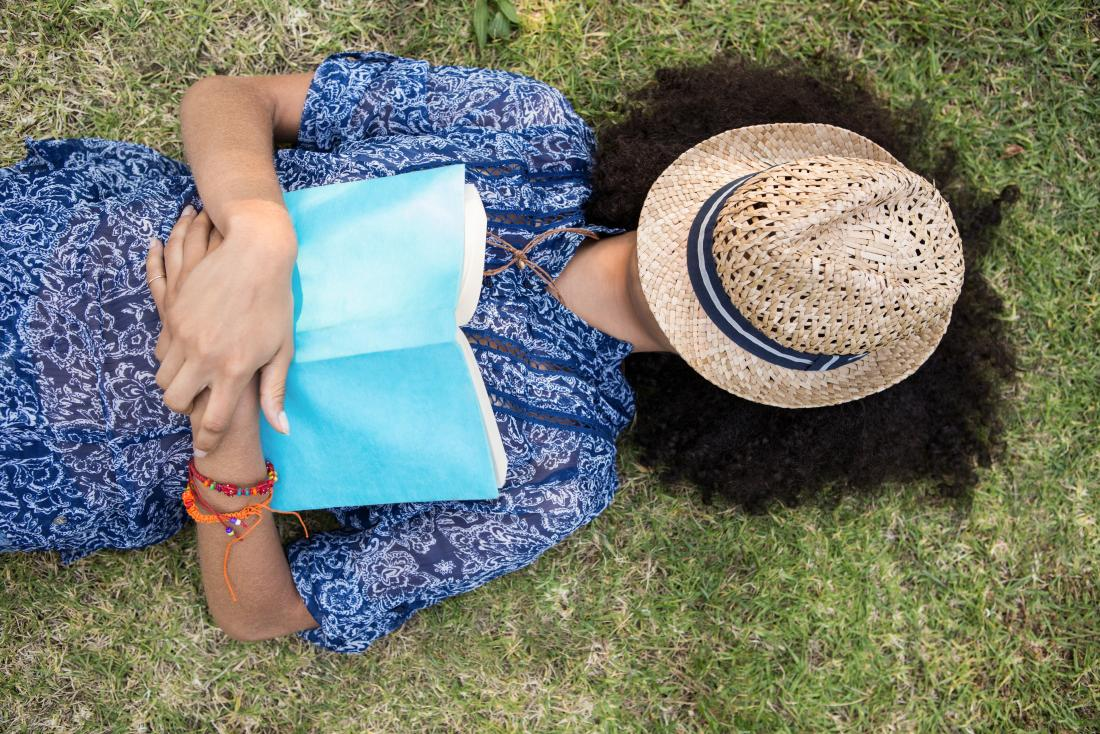 Woman lying outside on grass with book and hat covering head