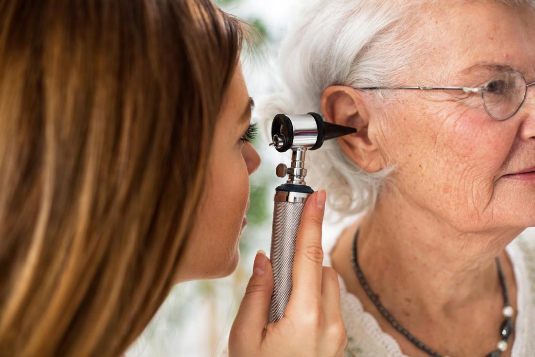 Elderly woman having ear inspected by doctor.