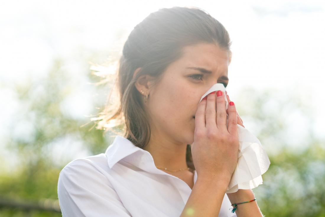 Woman outdoors with common allergic reaction blowing her nose.