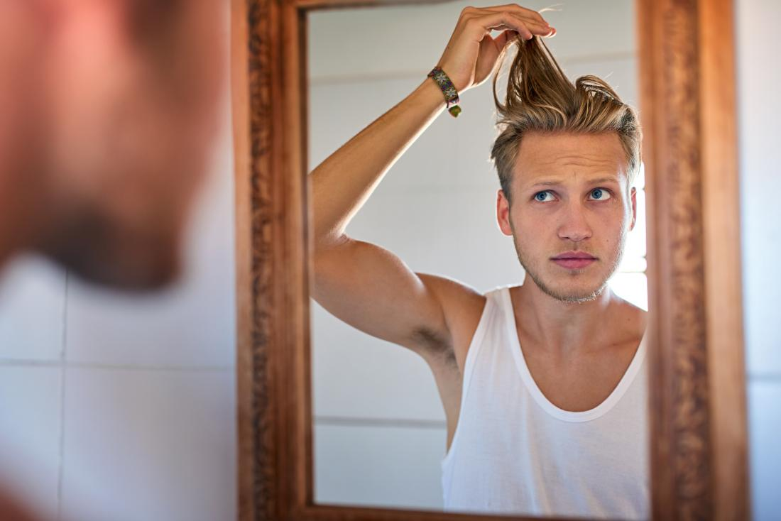 Man looking at oily hair in bathroom mirror, pulling strands of hair up.