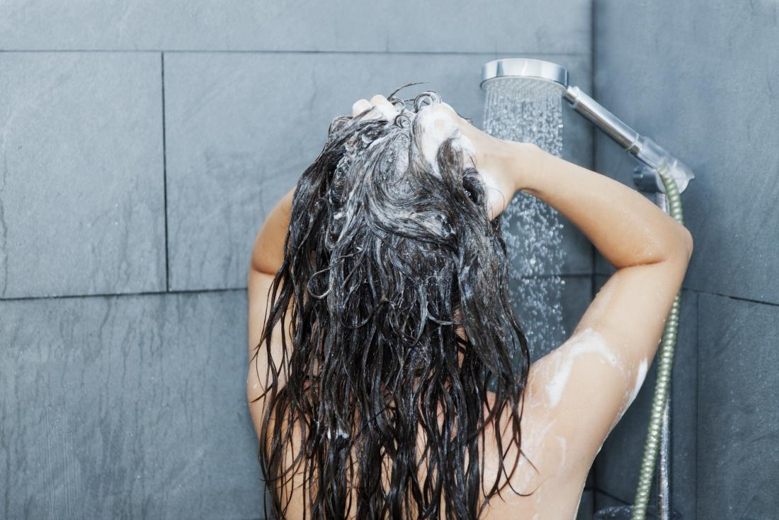 Woman washing her hair in the shower because she is concerned about oily hair.