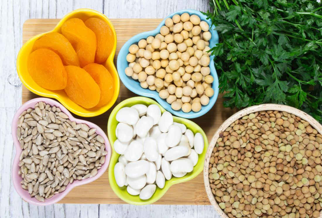 Iron rich foods including dried apricots, beans, seeds, chickpeas, lentils, and green leafy vegetables.
