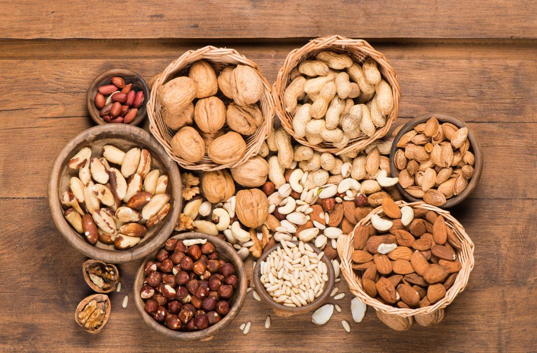 Various nuts in bowl on wooden table.