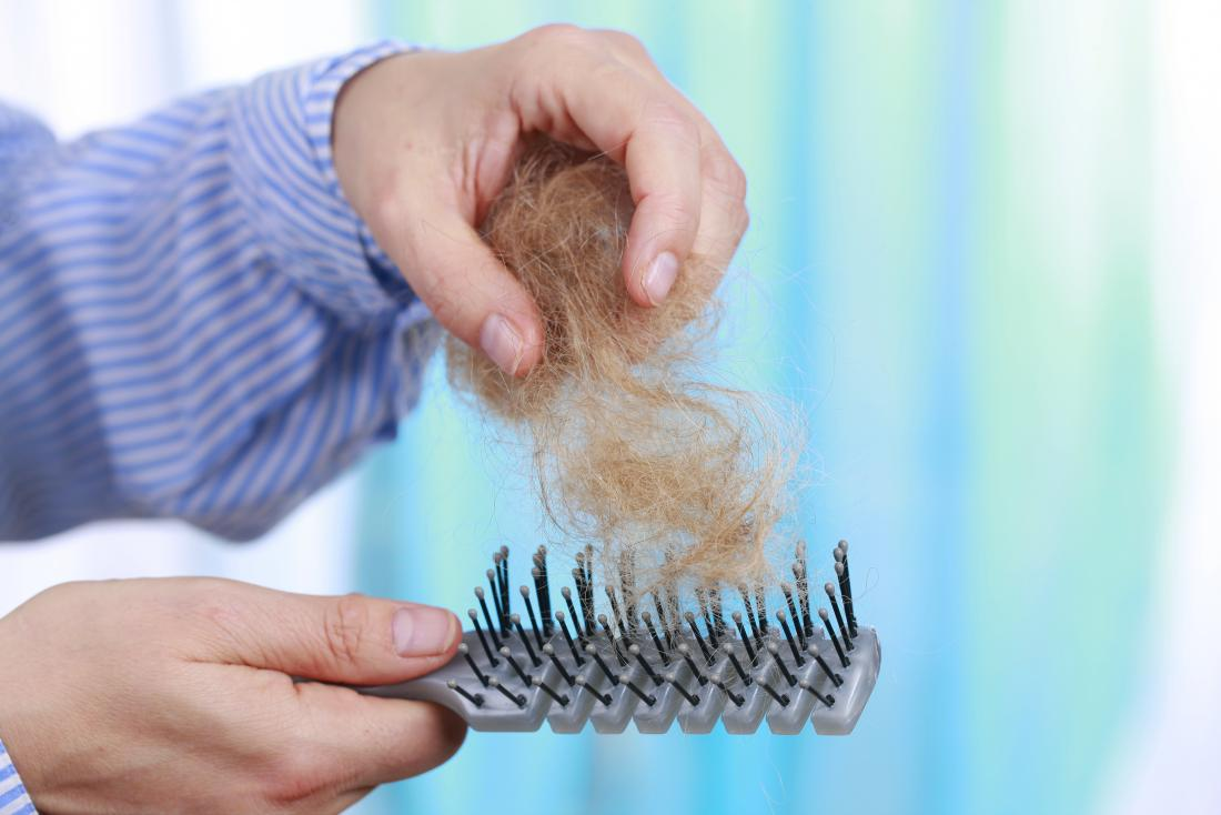 man pulling hair off of a hairbrush with telogen effluvium