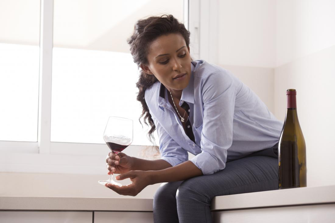 woman contemplating another glass of wine