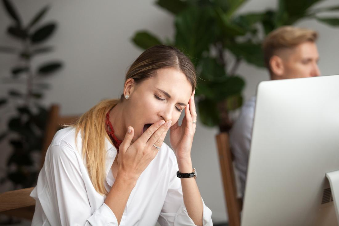young woman yawning while in front of computer