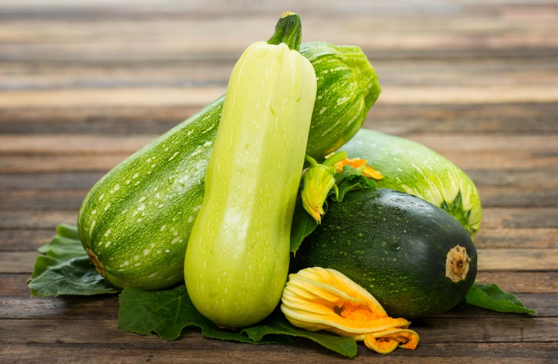 Zucchini piled up on wooden table with flowers.