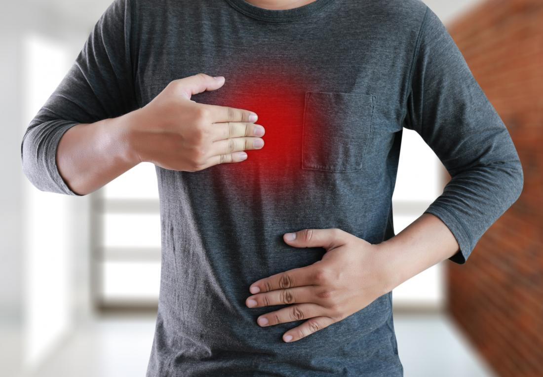 Man holding chest due to acid reflux