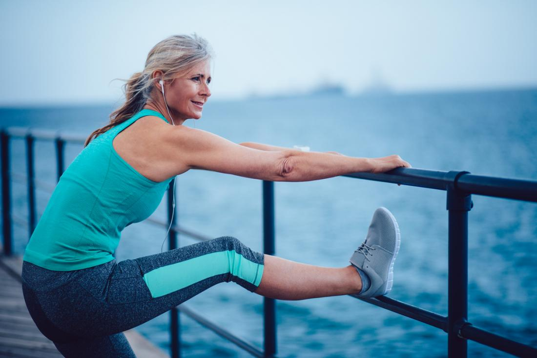 older woman stretching by sea
