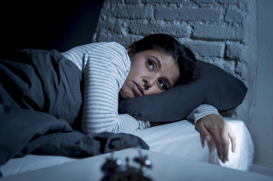 a woman in bed unable to sleep possibly due to an oncoming heart attack