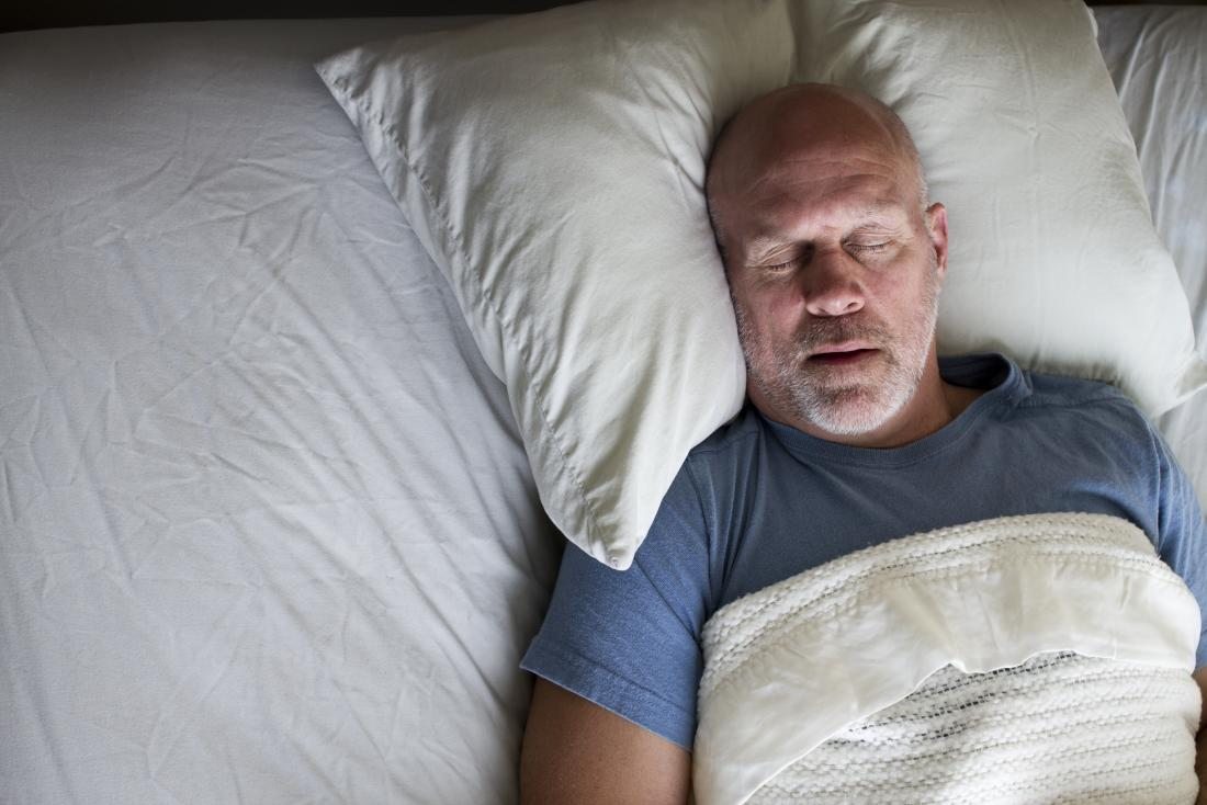 middle aged man asleep in bed