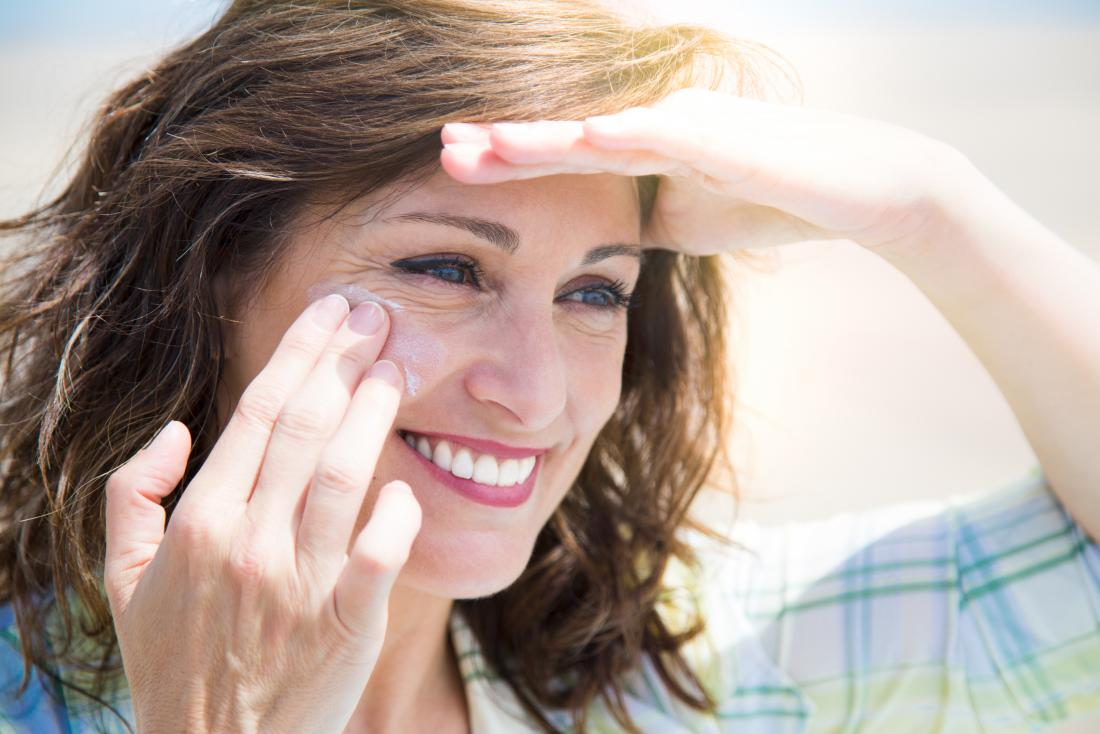 Middle aged woman applying sunscreen to face while shading eyes from sun and smiling.