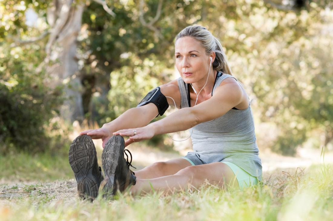 Woman sitting on ground outdoors touching toes performing foot flexion calf stretch