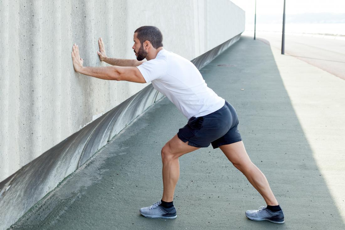 Man performing Gastrocnemius stretch for calf pain.