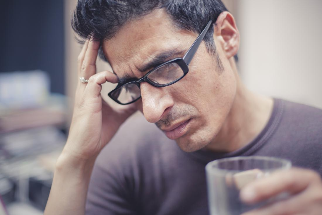 Man with headache on right side of head holding head and holding glass.