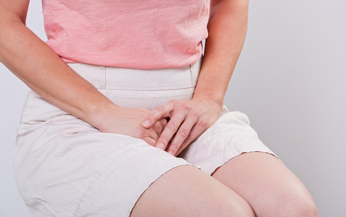 WOman with watery discharge sitting down covering crotch with hands.