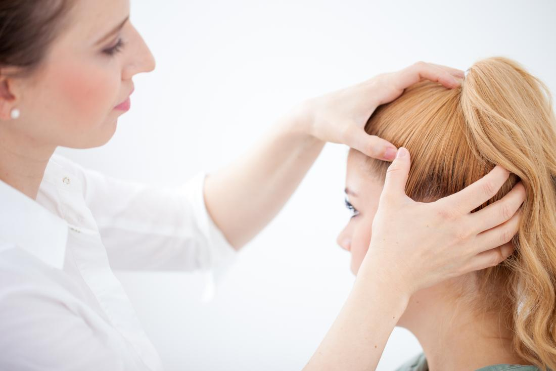 Doctor inspecting a patients hair for pilar cyst
