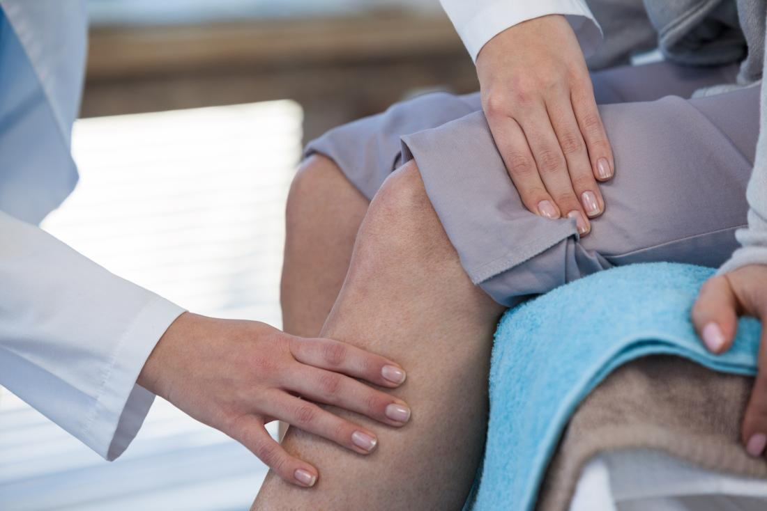 Doctor inspecting patients knee for joint pain as they sit on bed.