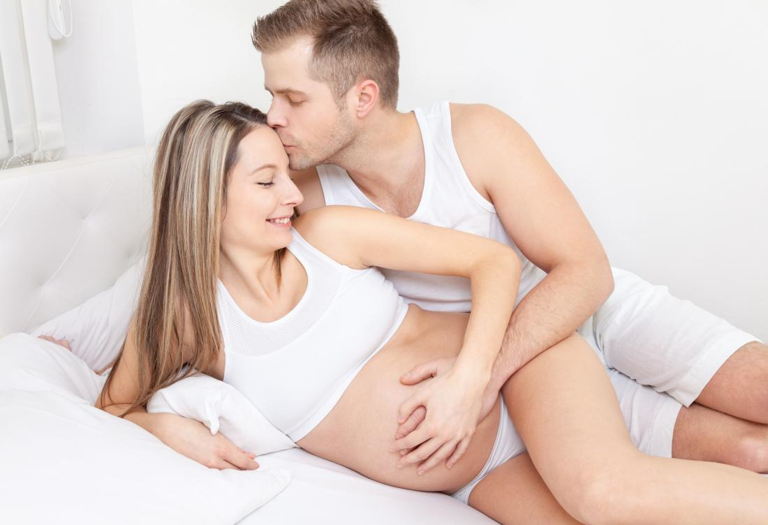 Pregnant woman in bed with partner considering sex during pregnancy