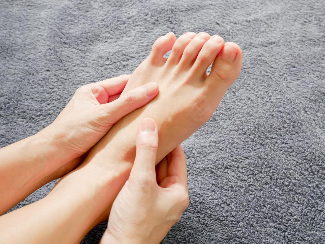 women holding her foot due to numbness in legs and feet