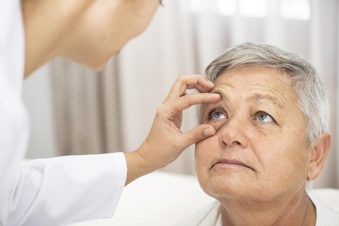 Person having their eye inspected by a doctor.