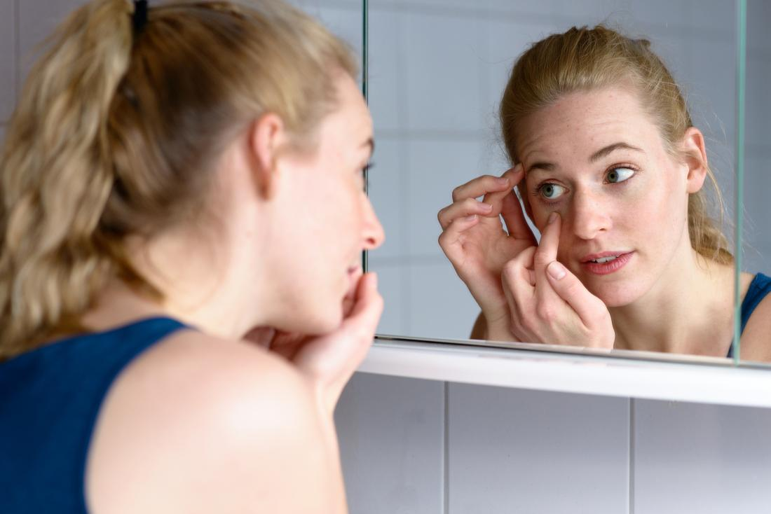 Woman inspecting ingrown eyelash in bathroom mirror
