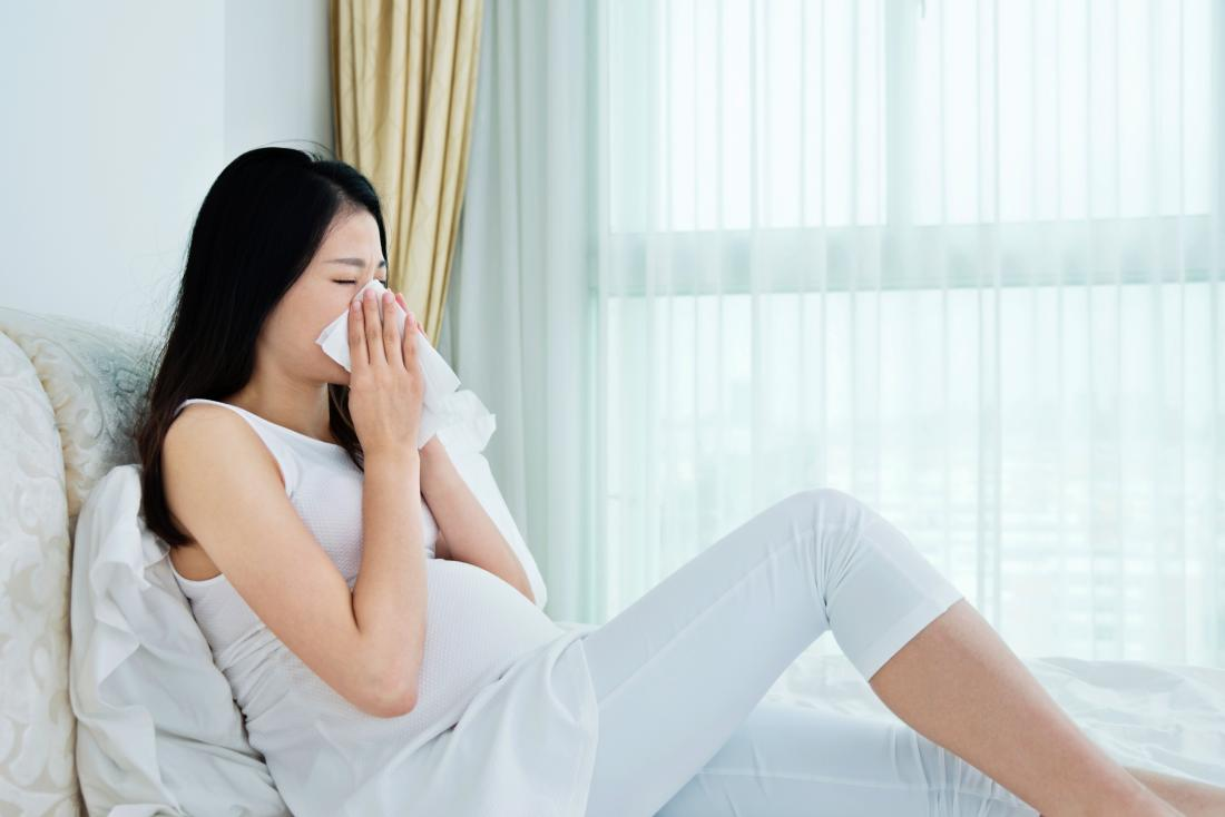 Pregnant woman sitting on bed sneezing and blowing her nose.