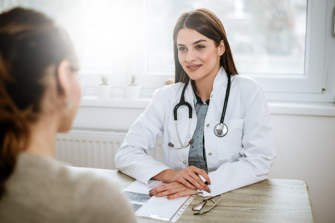 doctor at desk listening to patient in foreground