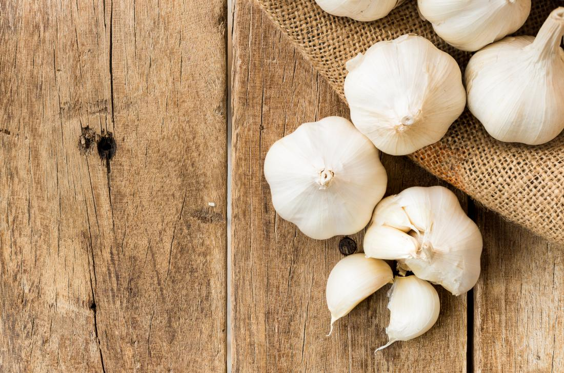 Garlic bulbs and cloves on wooden table to indicate allergy.