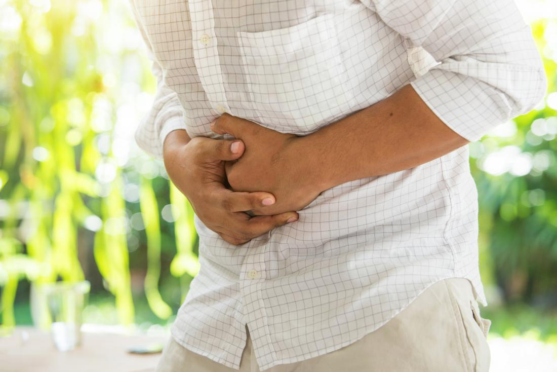Person with stomach pain after eating food they are allergic to