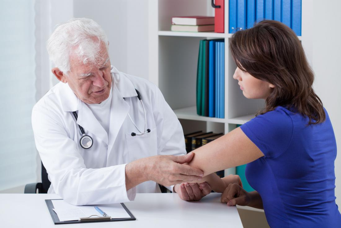 Woman having skin on elbow inspected by doctor.