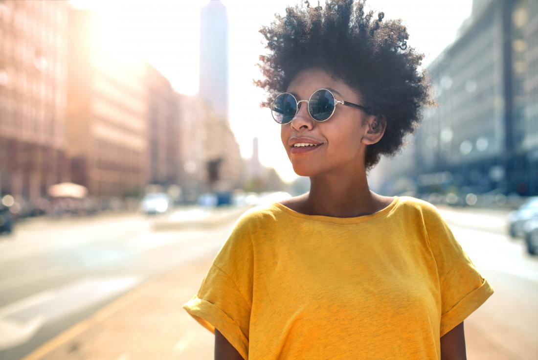 Woman outside in city wearing sunglasses.