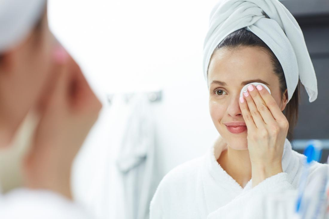 Woman removing eye makeup in the bathroom