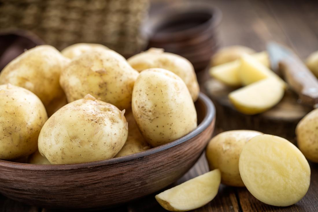 White potatoes in wooden bowl.