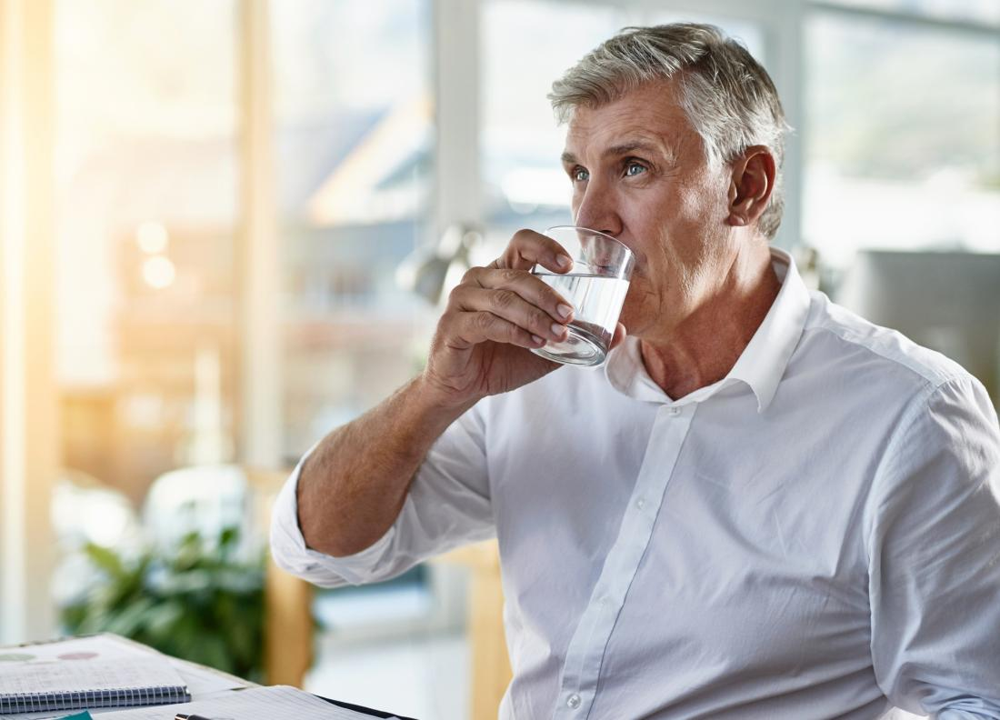 Mature man drinking glass of water.