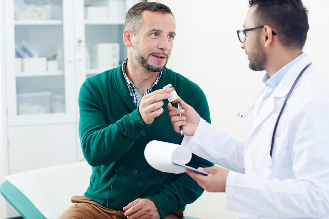 Man receieving prescription medication from doctor.
