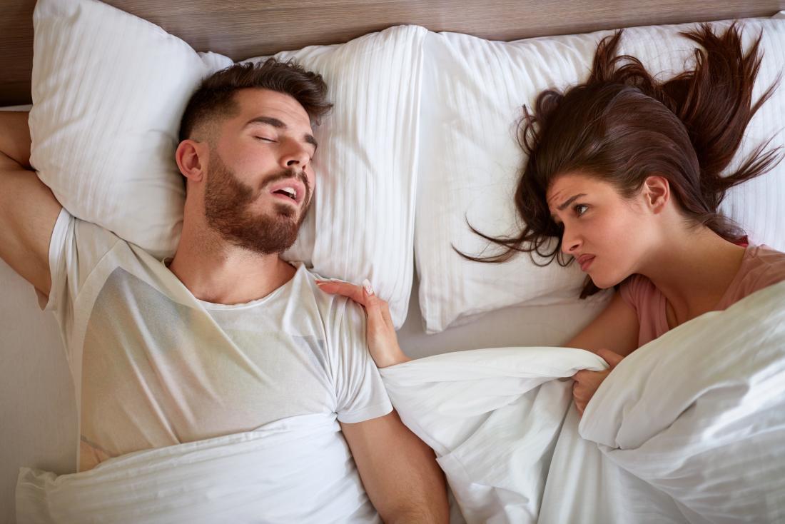 woman lying next to sleep talking man in bed