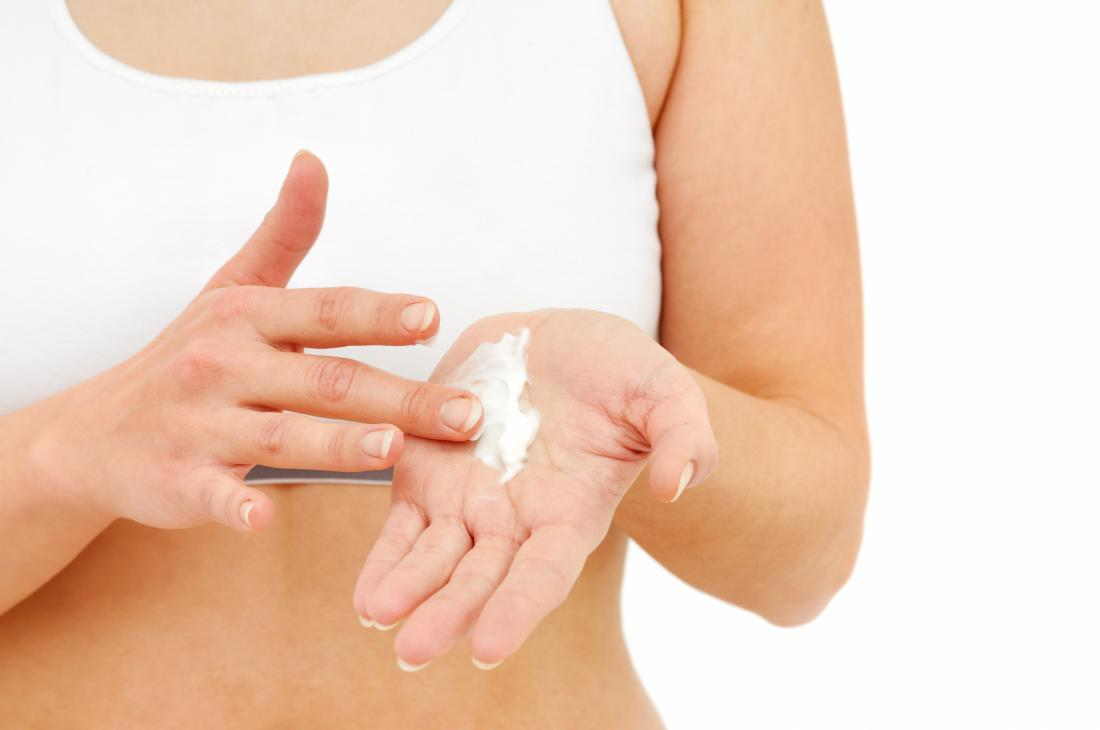 Woman putting cream on her hand for a milk blister