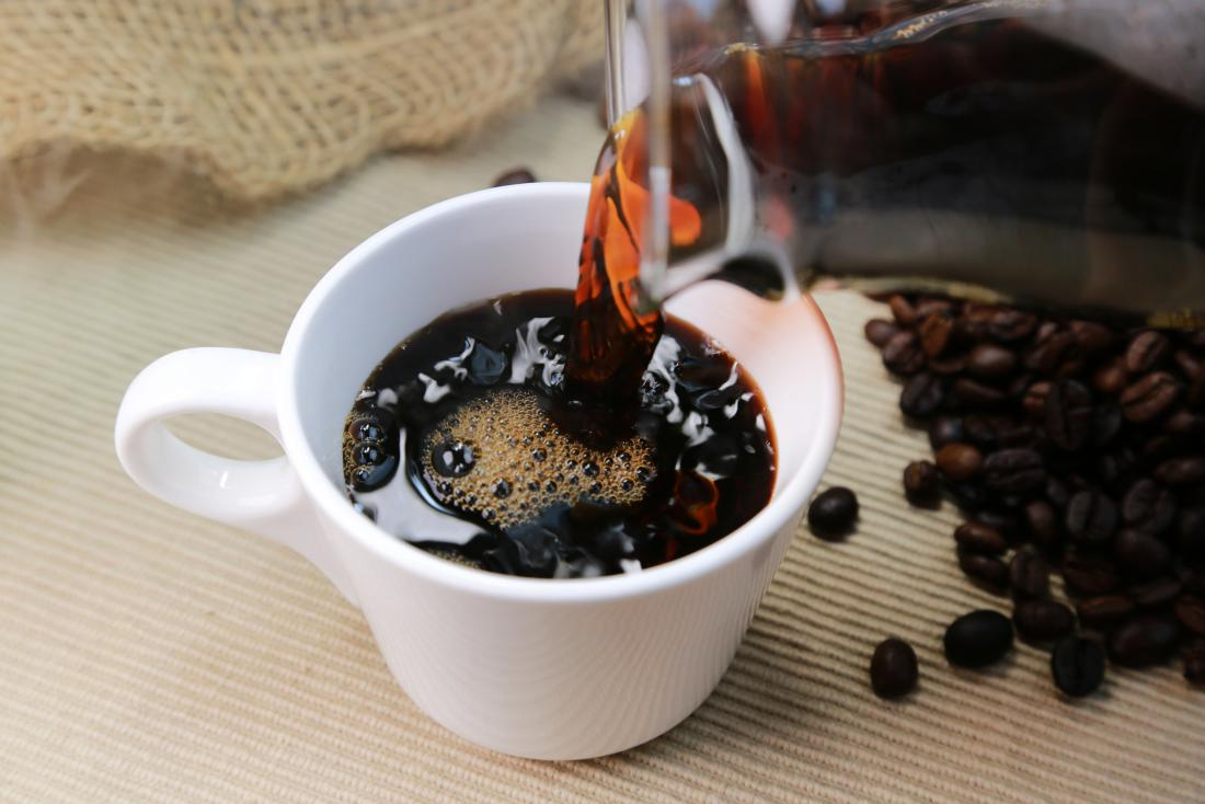 Caffeine in coffee being poured into cup surrounded by coffee beans.