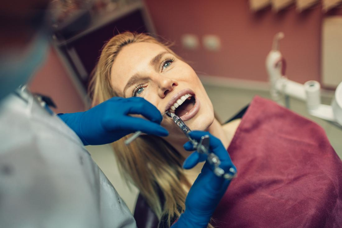 Woman receieving novocaine anesthesia from dentist during operation.