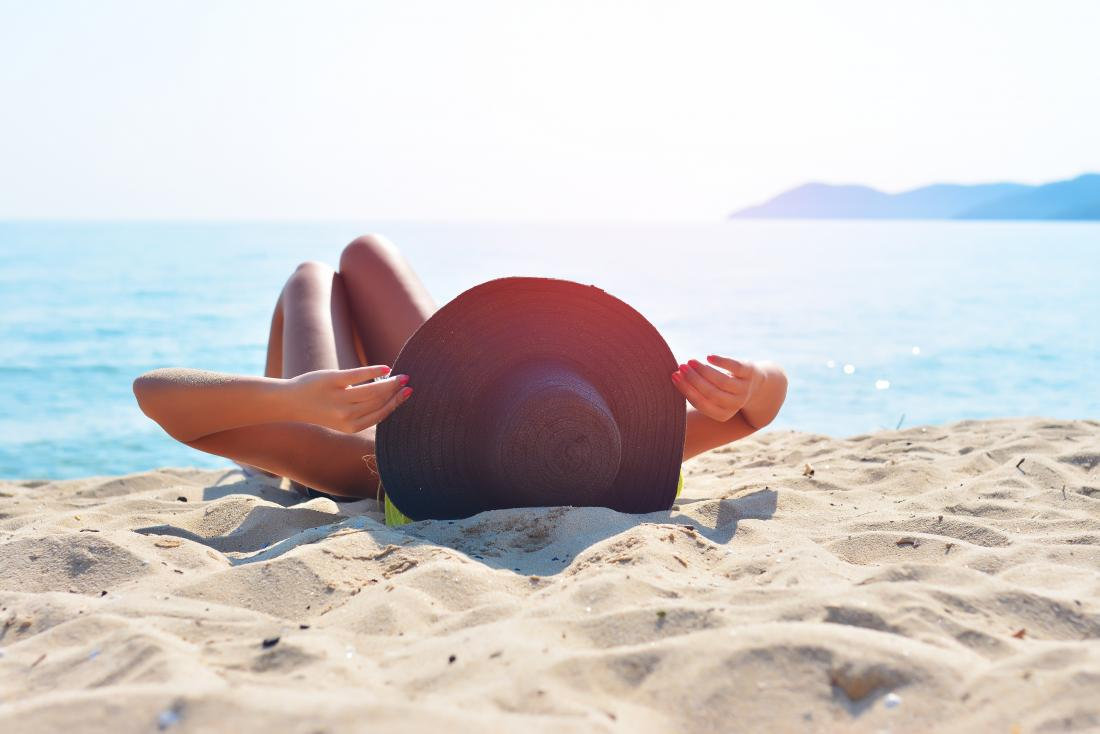 Woman sunbathing on the beach which may increase thin skin